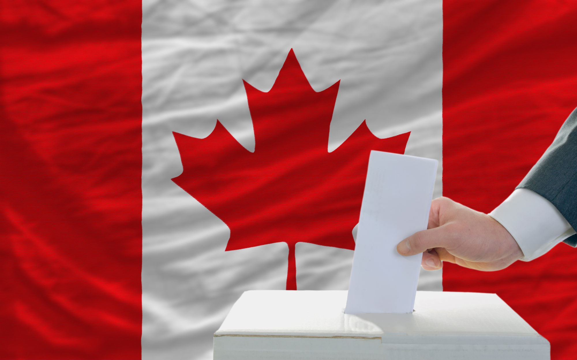 man-putting-ballot-in-a-box-during-elections-in-canada